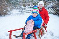 Kinder halten Geschenke im Schnee an Weihnachten