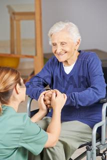 Seniorin im Rollstuhl hält Hände mit Krankenpflegerin
