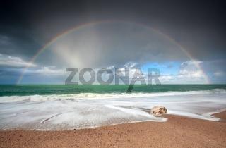rainbow over Atlantic ocean waves on coast