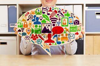 Frau hält Sprechblase mit Social Media Icons