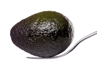 an avocado laying on a for, isolated on white