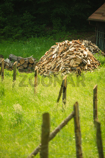 pile of wood behind wooden fence on a green grass