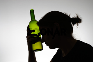 Alcoholic woman's silhouette with a wine bottle