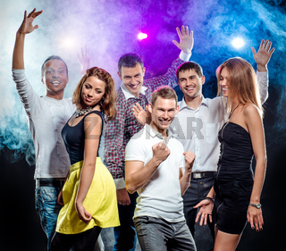 Cheerful group of young people dancing at party