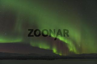 Nordlicht (Aurora borealis) ueber dem gefrorenen See Tornetraesk, Lappland