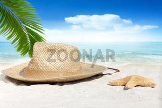 Strohhut und Seestern liegen unter Palmwedel am Strand