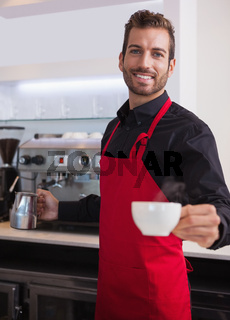 Happy young barista holding jug and cup of coffee