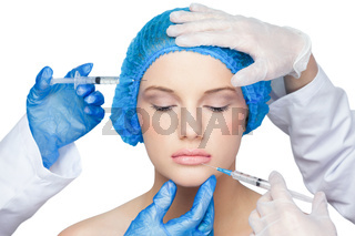 Surgeons making injection on calm blonde