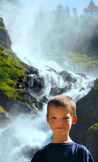 Portrait boy on summer waterfall background