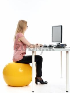 frau sitzt auf einem sitzball am schreibtisch