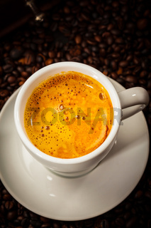 Espresso cup in coffee beans - top view
