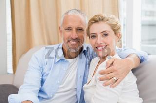 Happy couple smiling at camera on sofa