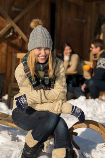 Young woman sitting winter snow sledge cottage