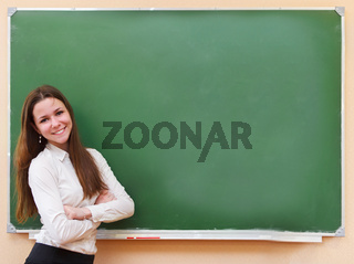 Student girl standing near blackboard in the classroom