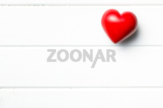 red stone heart on white wooden background