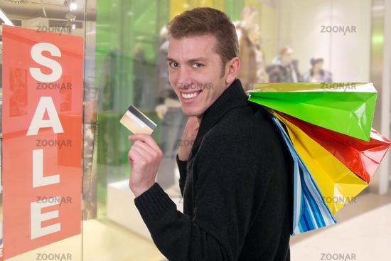 Lachender Mann beim Einkaufen mit Kreditkarte in Shopping Mall