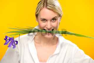 Woman bite spring iris flower between teeth