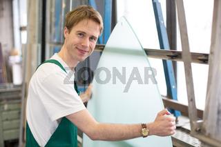 Worker in glazier's workshop handling glass