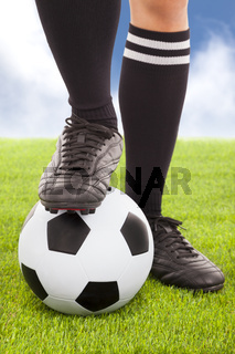 Soccer player's feet  and football with  sky background