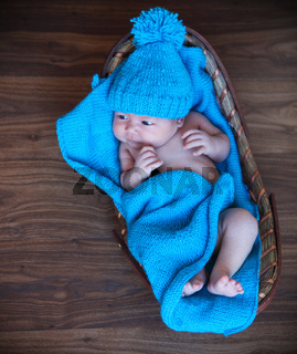 Baby boy laying on blue blanket in the basket