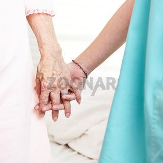 Krankenschwester hält Hand einer Patientin