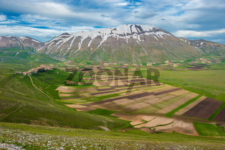 Piano Grande scenic fields and Sibillini mountains in Umbria, Italy