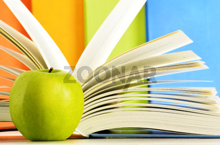 Composition with hardcover books and apple in the library