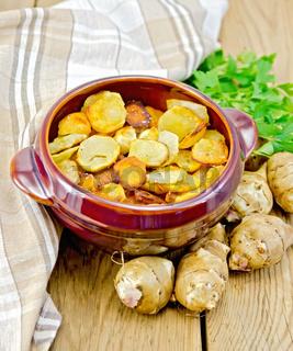Jerusalem artichokes fried in a pan on the board