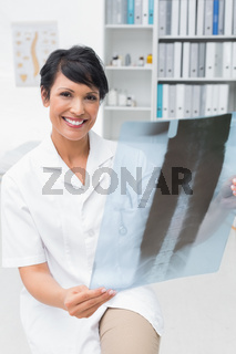 Portrait of a smiling female doctor examining x-ray