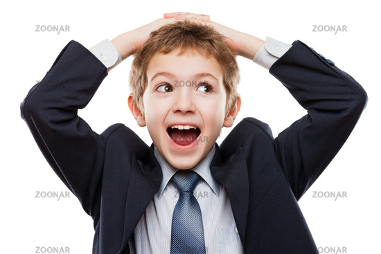 Amazed or surprised child boy in business suit holding hairs on head