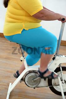 overweight woman exercising on bike simulator