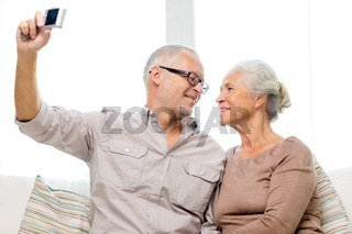 happy senior couple with camera at home