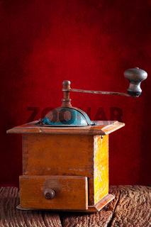 Alte mechanische Kaffeemühle vor rotem Hintergrund