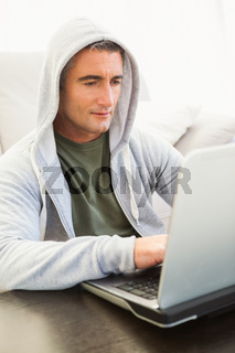 Smiling man in hood jacket using laptop