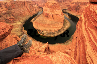 Pair of legs at Horseshoe bend overlook, adventure concept