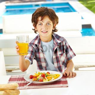 Kind isst Salat und trinkt Saft