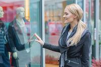 Happy young woman window shopping