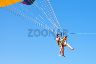 man and girl parasailing on parachute in blue sky