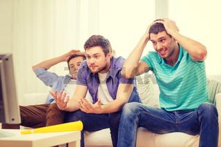 sad male friends with vuvuzela watching sports