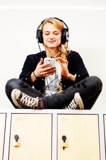 Hübsche blonde Studentin mit Kopfhörer