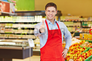 Marktleiter hält Daumen hoch im Supermarkt