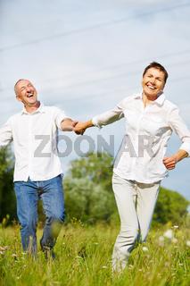 Lachende Senioren laufen über Wiese