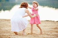 Tochter rennt auf Mutter zu am Strand