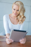 Beautiful young blond woman holding a tablet
