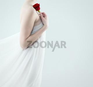 frau hält rote rose an die schulter