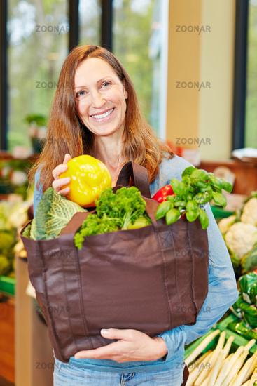 Lächelnde Frau kauft Gemüse