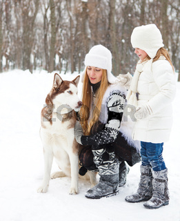 Happy young mother with daughter with huskies dog
