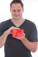 Young man smiling while holding a red gift box
