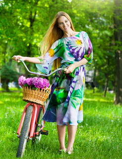 Beautiful blond woman wearing a nice dress having fun in park with bicycle carrying a beautiful basket full of peony flowers. Vintage scenery