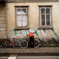 Person securing a bicycle to an urban building